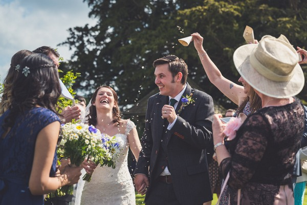 Bride and groom laughing as confetti is thrown over them