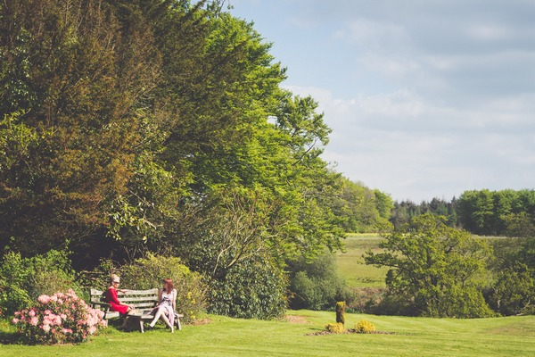 Wedding guests sitting on bench in garden of Buckland House