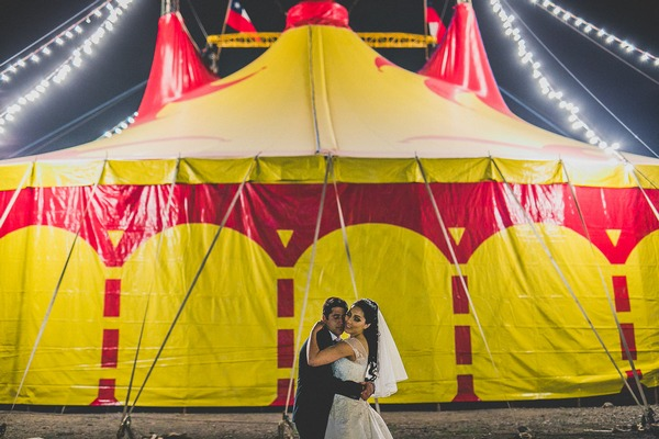 Bride and groom in front of circus tent