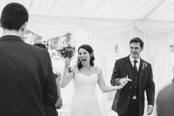 Happy bride and groom enter wedding breakfast in marquee