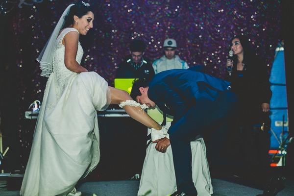 Groom taking of bride's garter with teeth