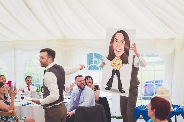Best men holding caricature of groom