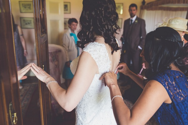Lady doing up back of bride's wedding dress