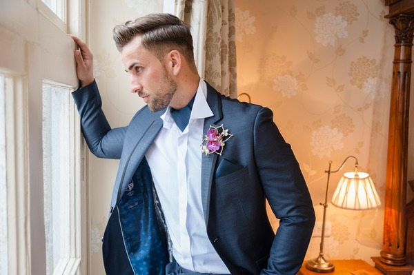 Groom in blue suit looking out of window