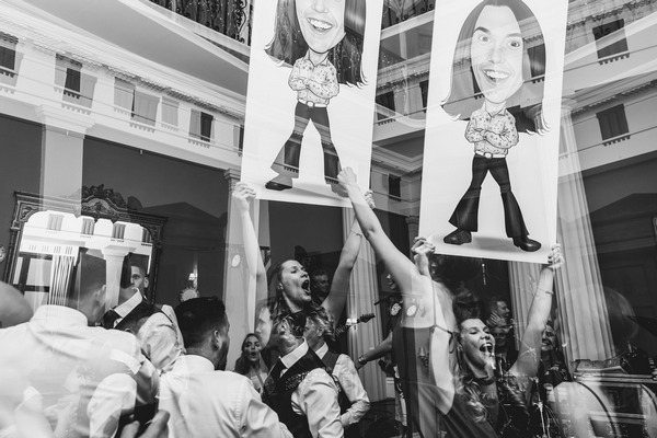 Wedding guests holding up caricatures of bride and groom