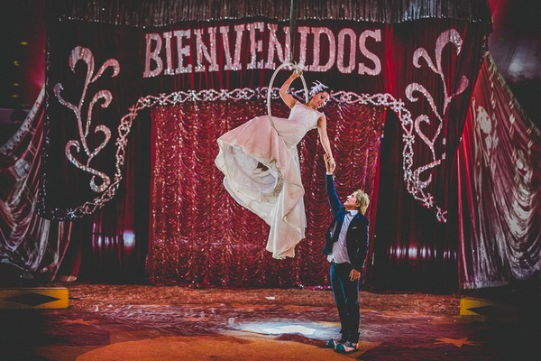 Groom holding bride's hand on trapeze