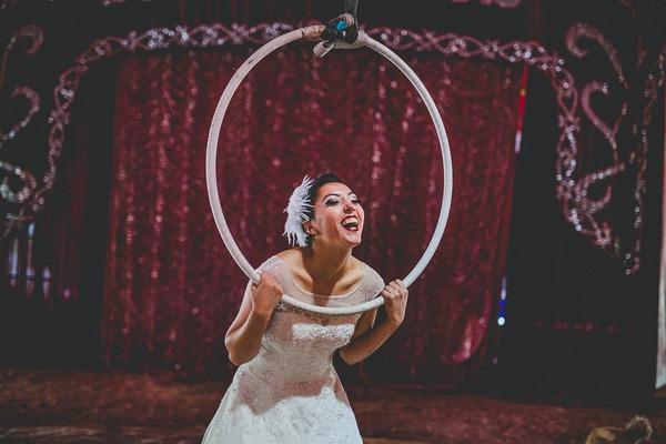Bride poking head through trapeze hoop