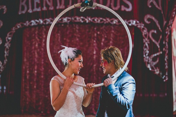 Bride and groom holding trapeze hoop