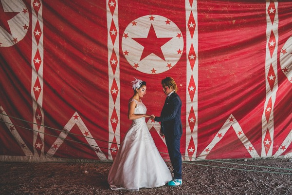 Bride and groom in front of red circus curtain