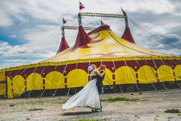 Groom lifting bride in front of circus tent
