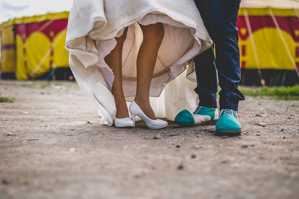 Bride and groom's legs with groom in clown shoes