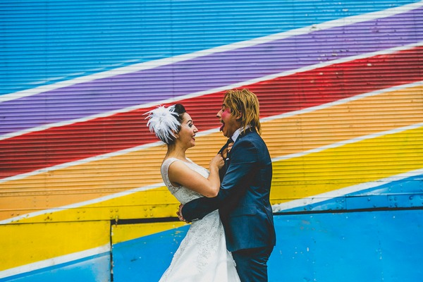 Bride and clown face groom in front of colourful wall