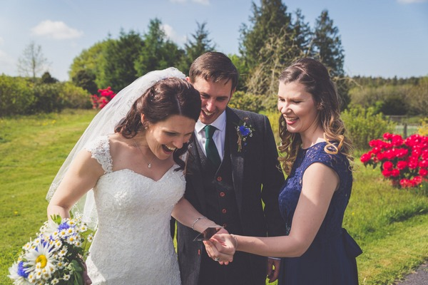 Wedding guest showing bride and groom a picture