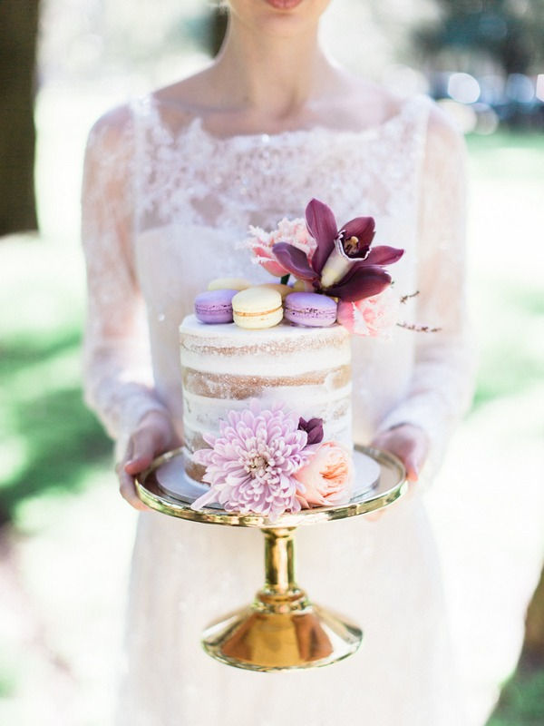 Bohemian bride holding wedding cake with flower and macaroons