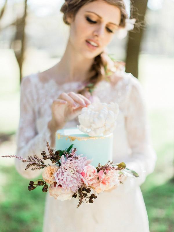 Bohemian bride holding blue wedding cake