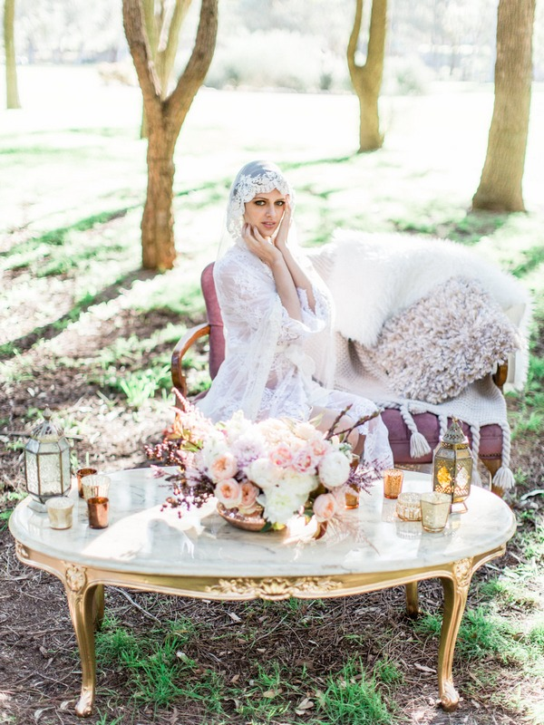 Bohemian bride with lace robe and veil sitting at table in woodland
