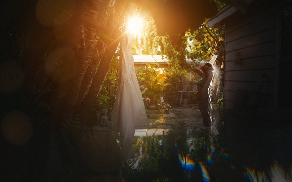 Bride showering next to wedding dress hanging from tree - Picture by Richards and Co Photography
