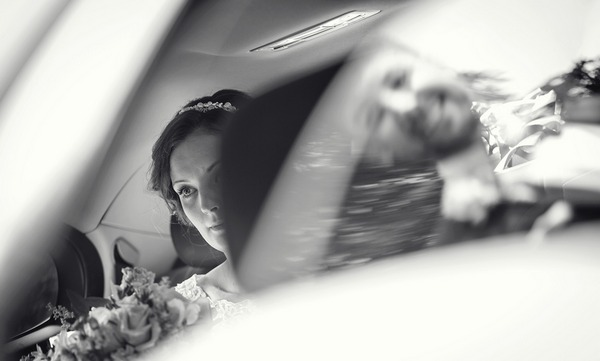Bride sitting in back of wedding car with reflection of groom in window - Picture by Sean O'Dell Photography