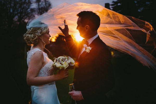 Groom holding up hand as sun shines through bride's veil - Picture by Kevin Belson Photography
