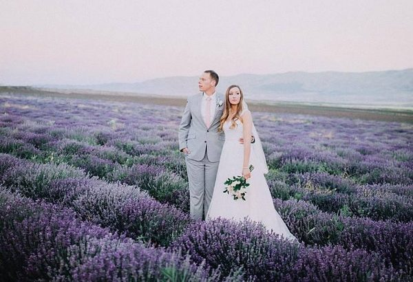 Bride and groom standing in field of lavender - Picture by Cassandra Farley Photography