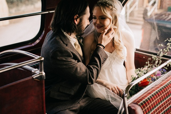 Bride and groom sitting on back of bus - Picture by Let Love Flourish