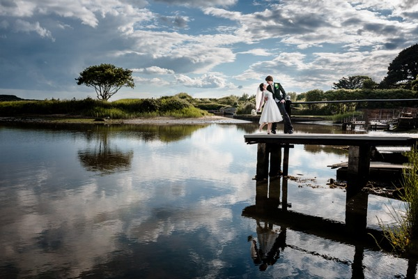 Bride and groom standing on jetty over lake - Picture by Libra Photographic