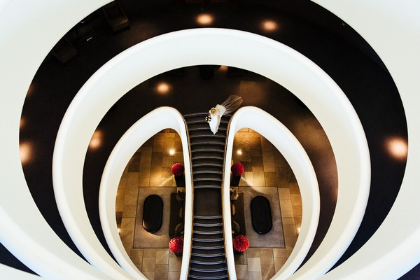 Bride walking down cool staircase at The Aviator Hotel - Picture by Lyndsey Goddard Photography