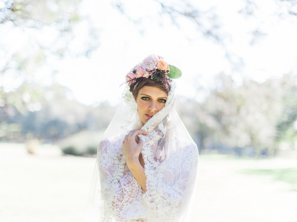 Bohemian bride with flower crown pulling lace veil over face