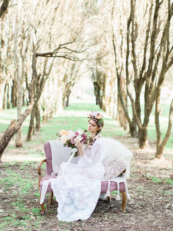 Bohemian bride sitting on couch in woodland