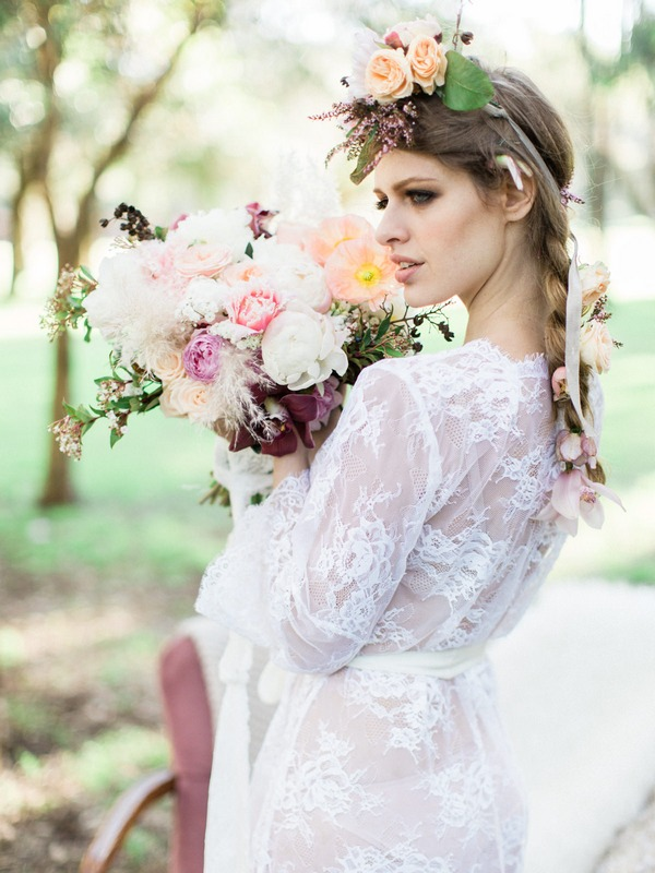 Bohemian bride in lace wedding robe holding bouquet