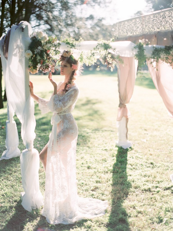 Bohemian bride looking at flowers on ceremony structure