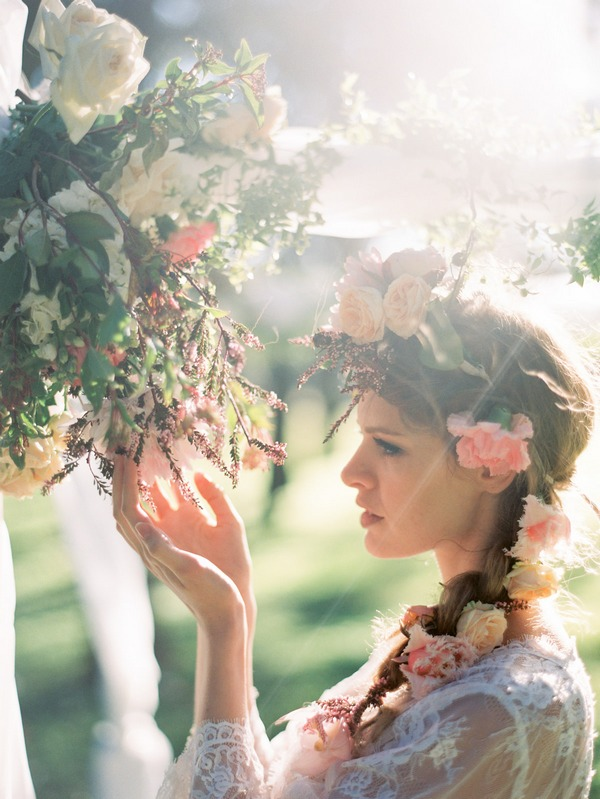 Bohemian bride looking closely at flowers