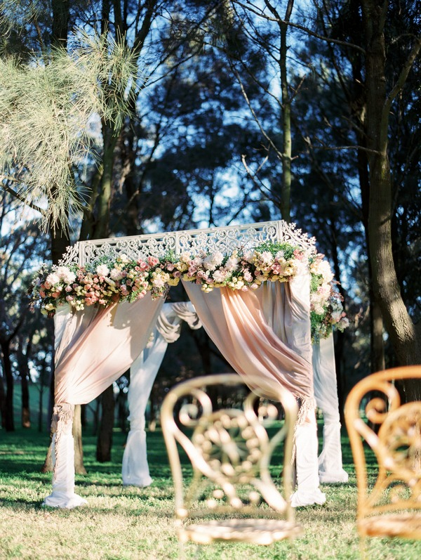 Elegant outdoor ceremony structure with flowers and drapes