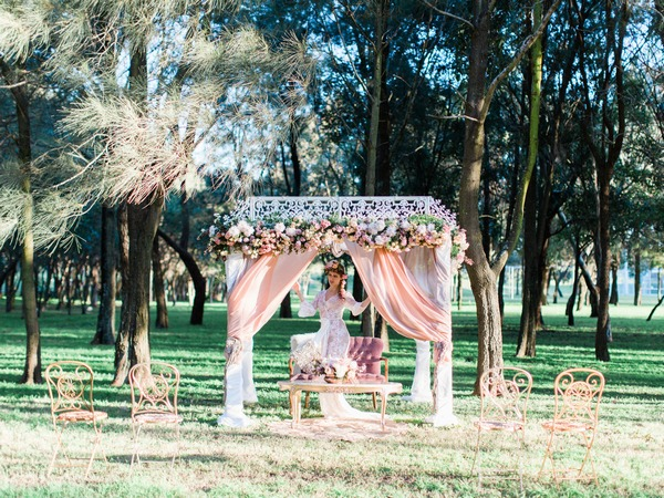 Bohemian bride standing under ceremony structure in woodland