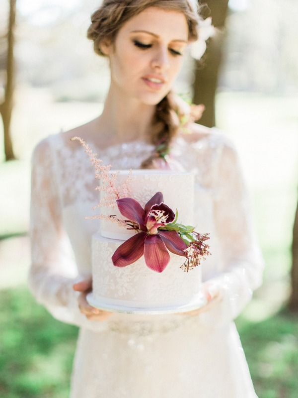 Bohemian bride holding wedding cake with large red flower