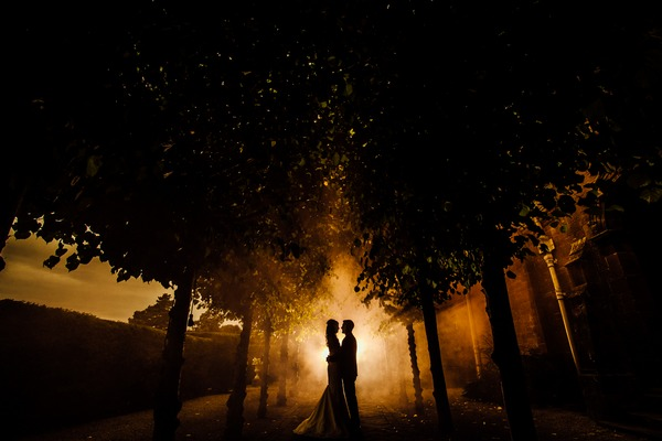 Silhouette of bride and groom standing in middle of row of trees - Picture by Jonny Draper Photography