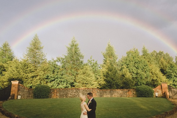 Bride and groom with double rainbow overhead - Picture by Murray Clarke