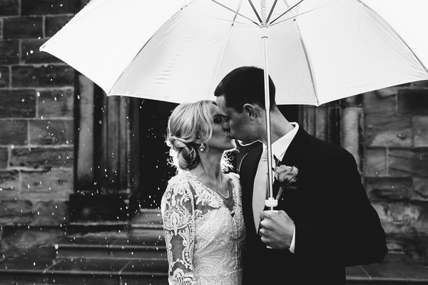 Bride and groom kissing under umbrella - Picture by Andy Turner Photography