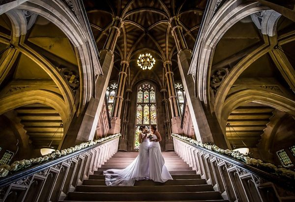 Two bride standing on steps in Rochdale Town Hall - Picture by Peter Anslow Photography