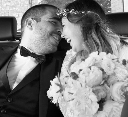 Bride and groom laughing in back of wedding car - Picture by Lea Salomone Creative