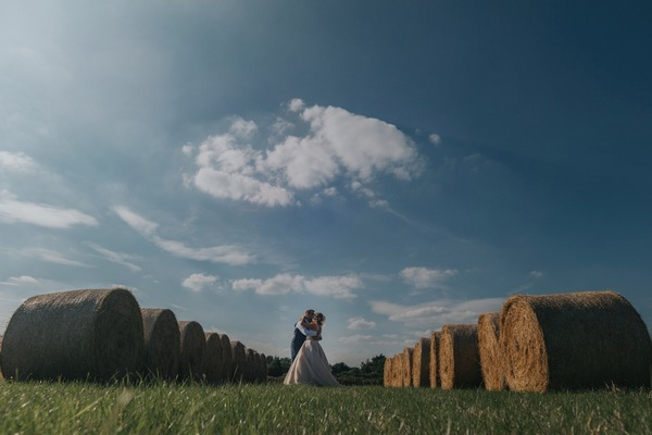 Bride and groom kissing in middle of large round hay bales - Picture by Emma and Rich