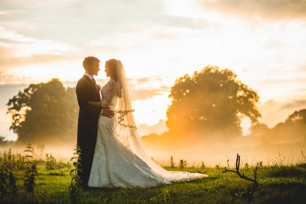 Bride and groom standing in field with hazy sunshine and mist - Picture by Tobiah Tayo Photography