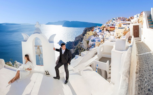 Bride and groom posing with Santorini in background - Picture by Clane Gessel Photography