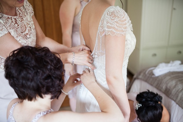 Bridesmaids doing up back of bride's dress