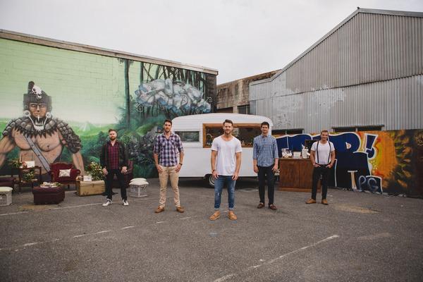 Men standing in front of caravan bar