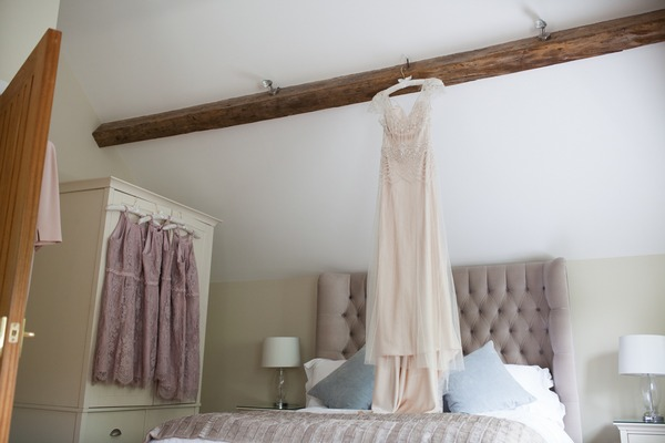 Wedding dress hanging from beam in cottage at Packington Moor