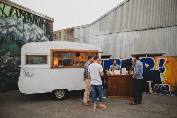 Men drinking whisky by caravan bar