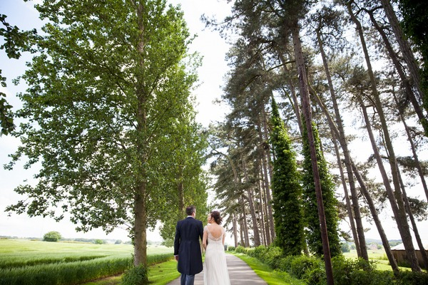 Bride and groom walking past trees at Packington Moor