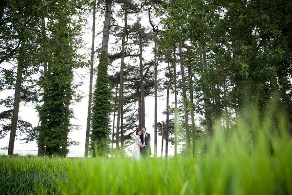 Bride and groom in front of tall trees at Packington Moor