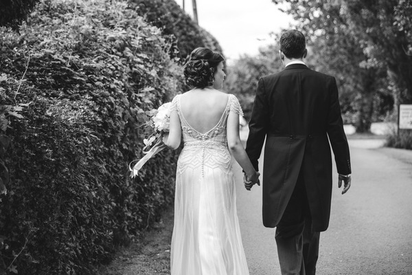 Bride and groom walking holding hands at Packington moor